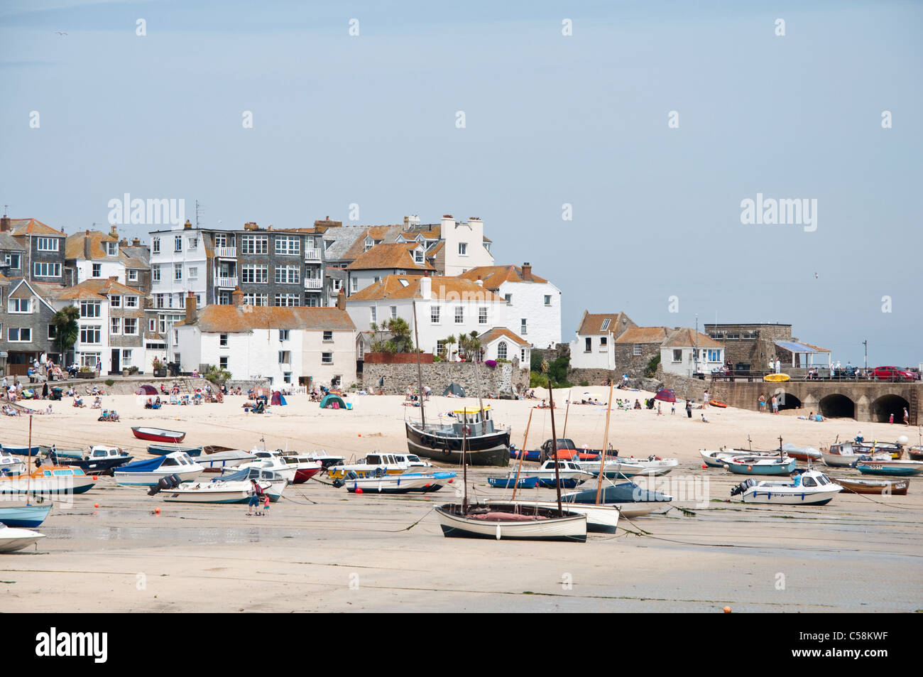 St Ives harbour at low tide with sailing boats beached on the sandy shore. Cornwall, England, UK. ( muted tones - Stock Image