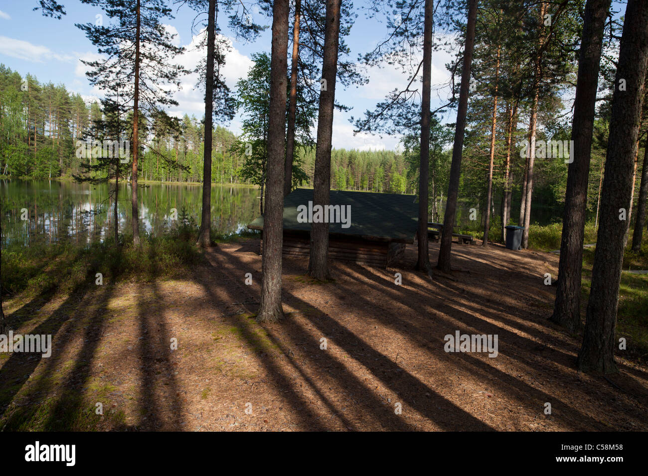 Camping site by a forest lake .  Small wooden bivouac shelter offers shelter for rain , Finland - Stock Image