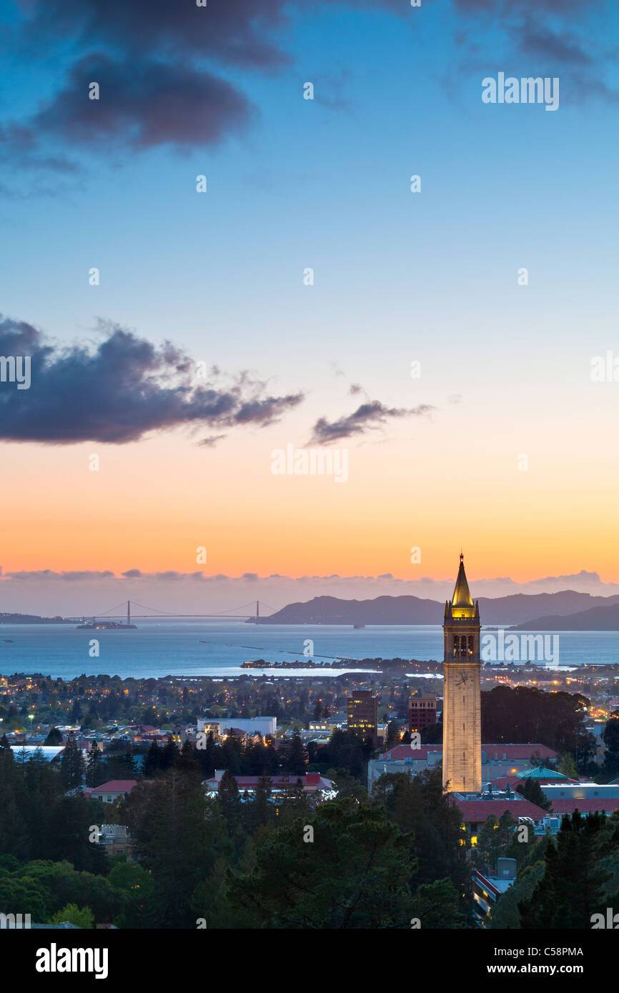 The Campanile (Sather Tower) of UC Berkeley aglow at sunset with the San Francisco Bay in the background. - Stock Image