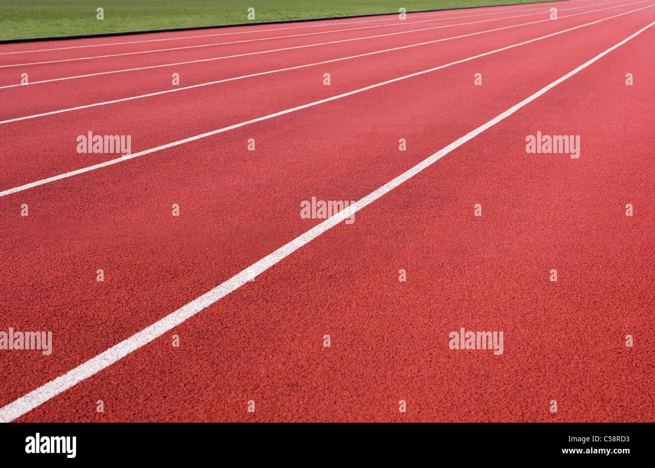 Running lanes of an athletics track stretching off into the distance. - Stock Image