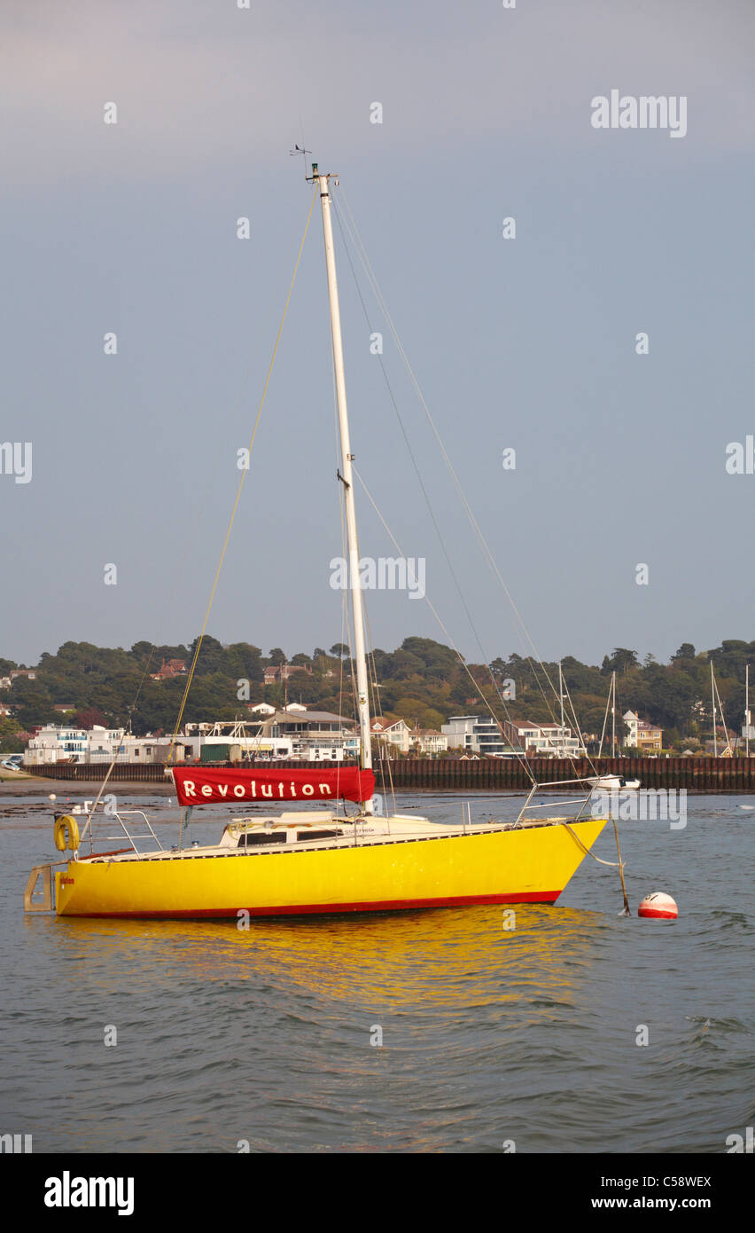 Yellow hulled yacht named Revolution anchored at Sandbanks, Poole in April - Stock Image