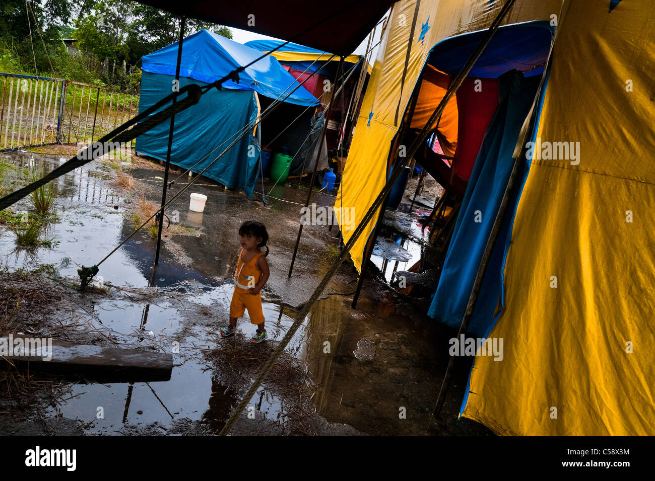 A little Colombian girl walks through puddle at the Circo Anny, a family run circus wandering the Amazon region - Stock Image