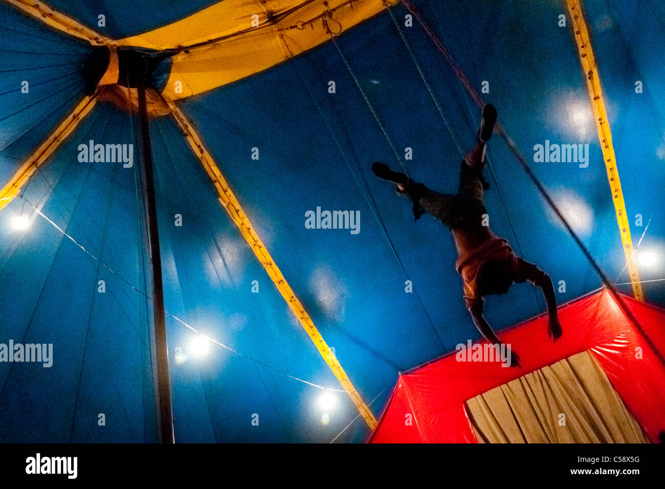 Raimundo performs a flying trapeze act at the Circo Anny, a family run circus wandering the Amazon region of Ecuador. - Stock Image