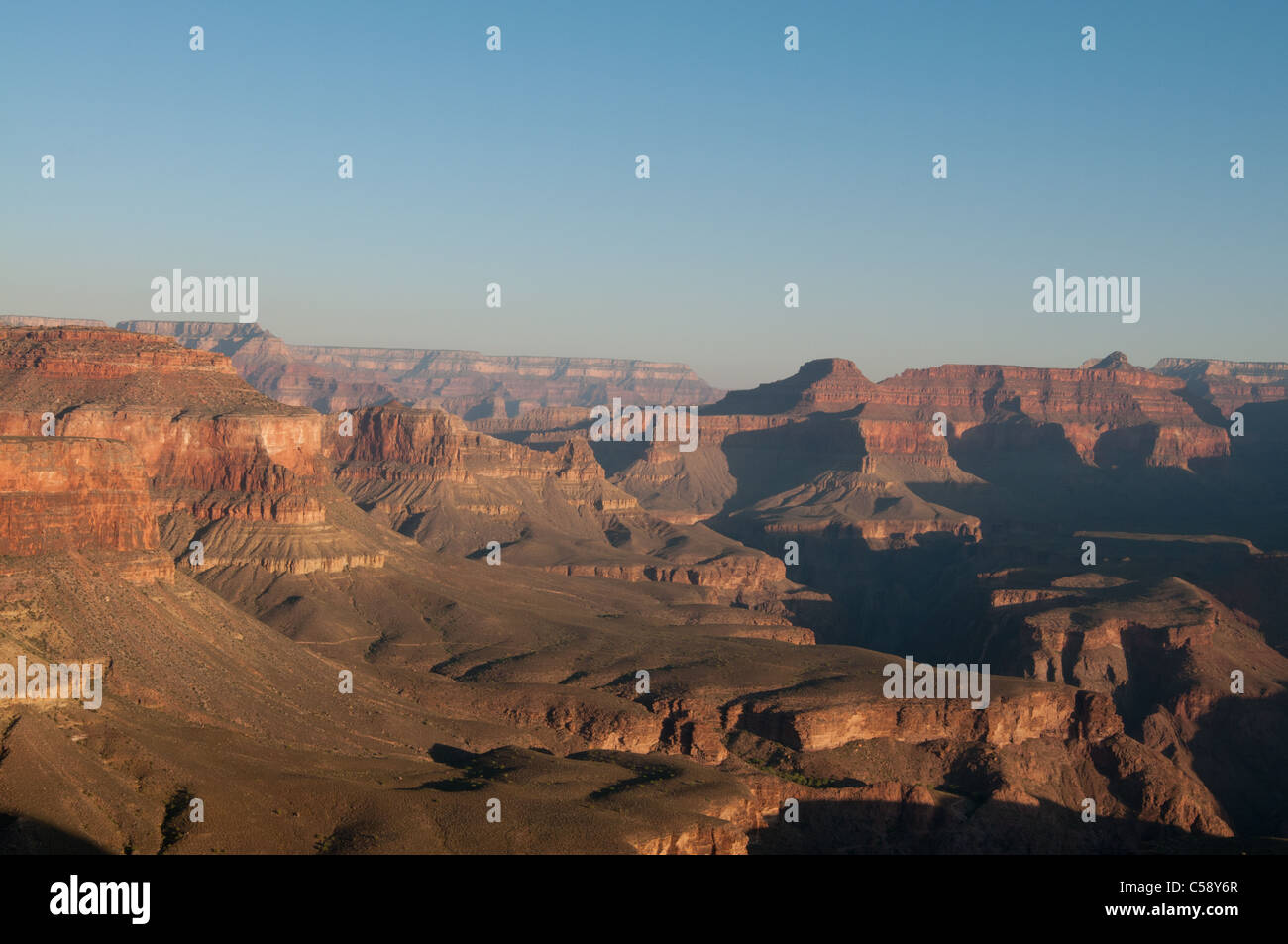 The sun rises over a valley on the South Kaibab Trail in Grand Canyon National Park - Stock Image