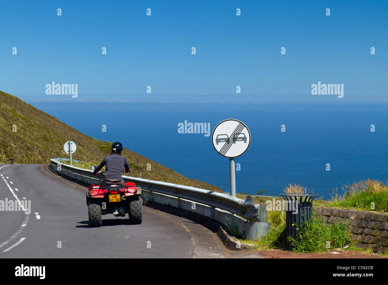 Man in ATV driving past Lagoa do Fogo - the Fire Lake, a famous crater lake in São Miguel island, Azores. - Stock Image
