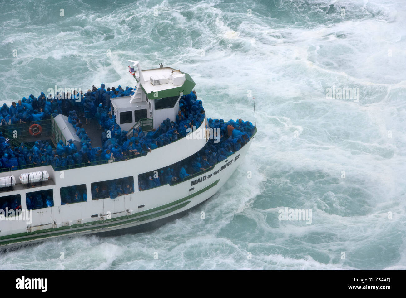 tourists on maid of the mist boat on the niagara river approaching niagara horsehoe falls ontario canada - Stock Image