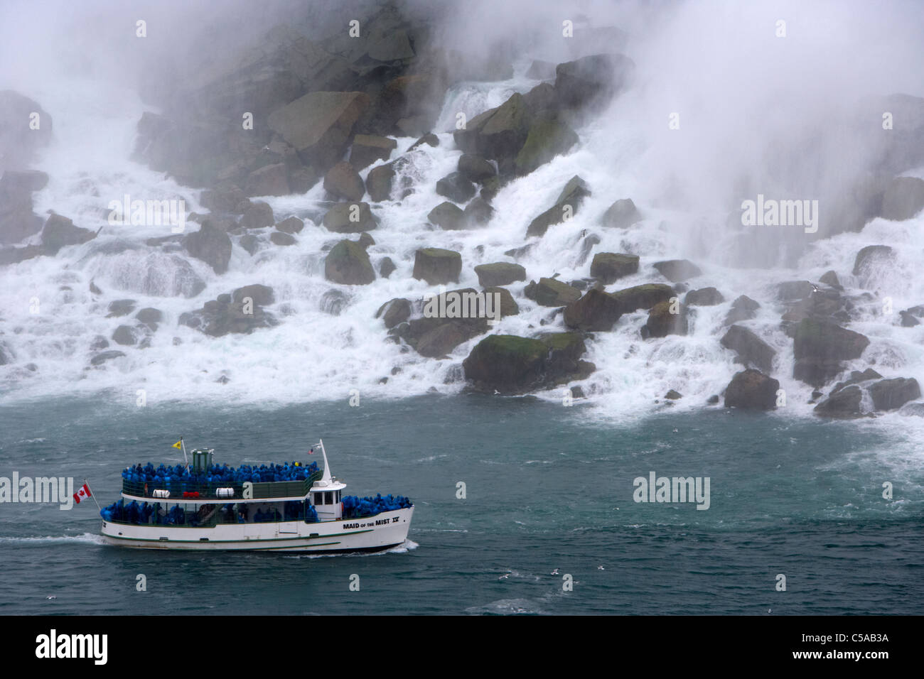 maid of the mist boat below the american and bridal veil falls rock pile niagara falls ontario canada - Stock Image