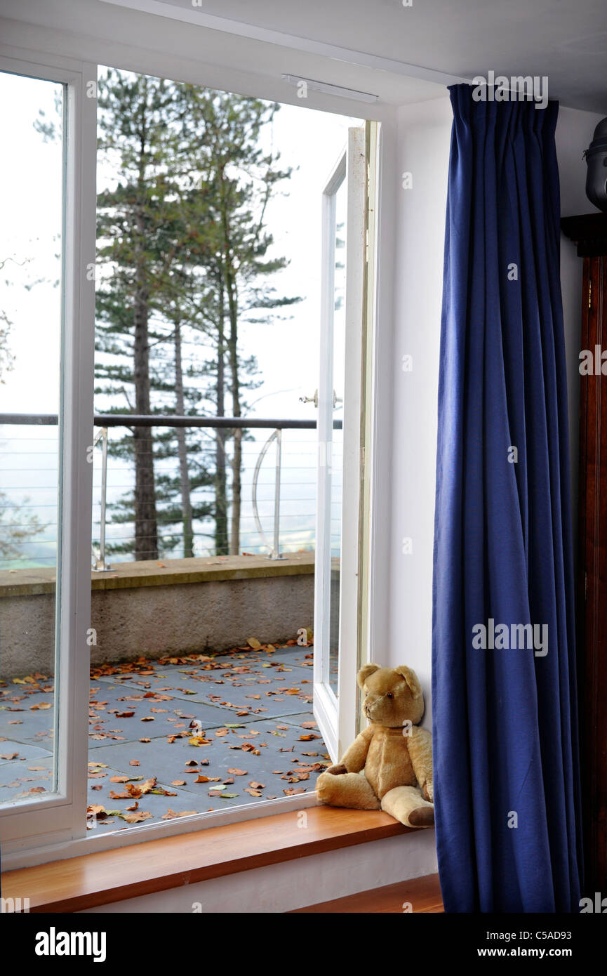 Teddy bear in the window of a house during autumn UK - Stock Image