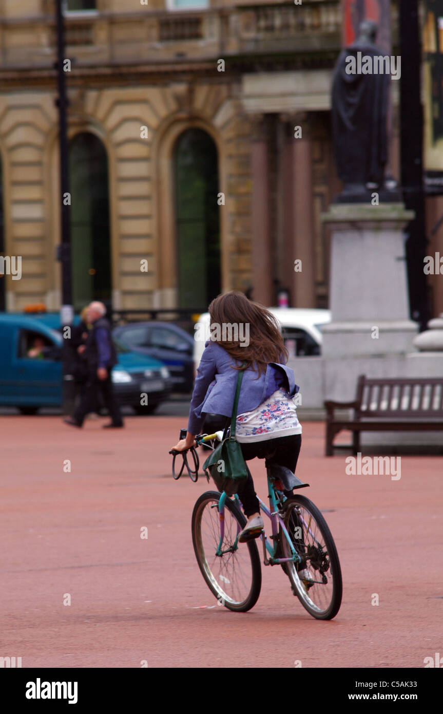 Cycling through George Square, Glasgow - Stock Image