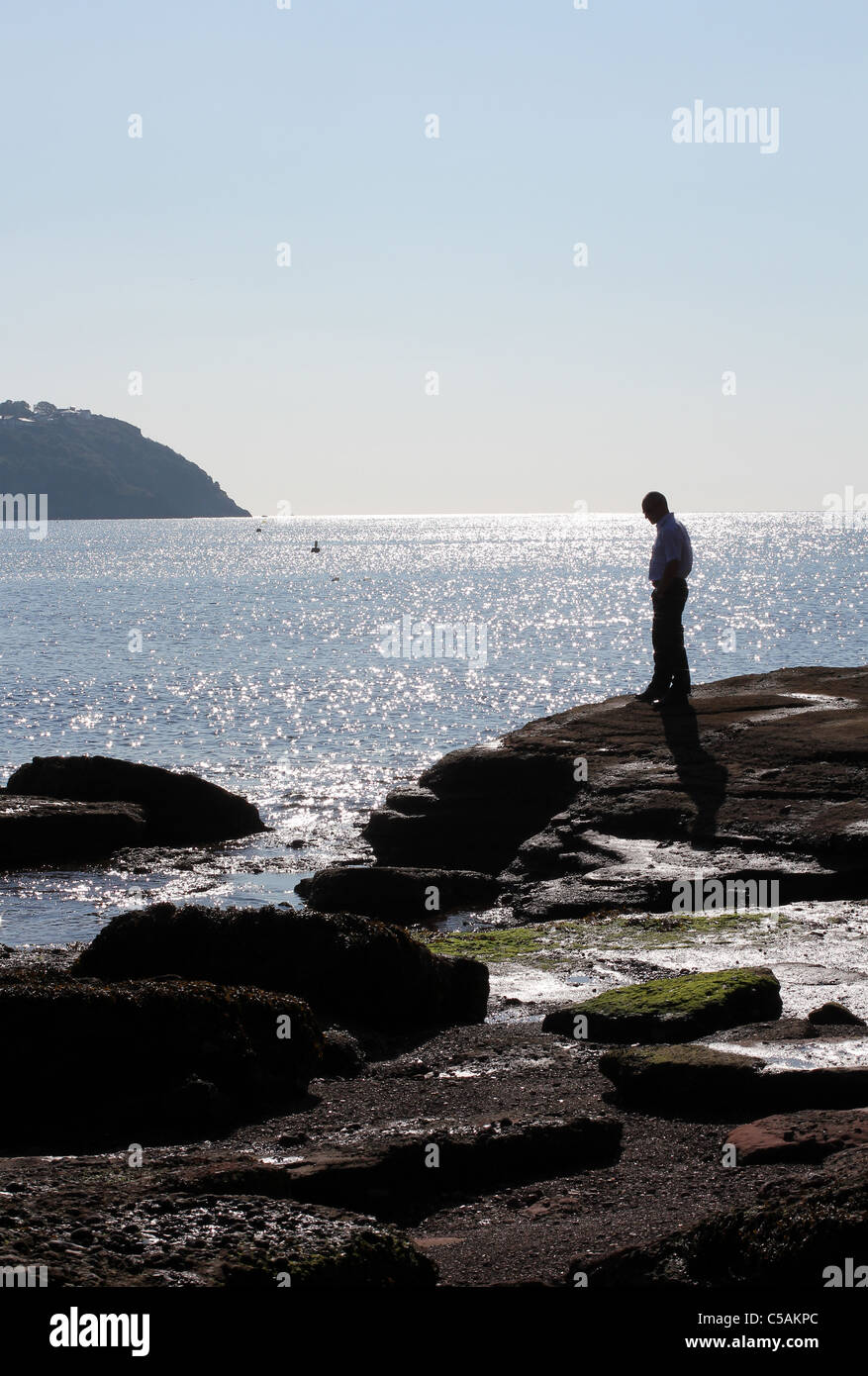 A solitary man surveys rocks at Torquay in Devon,Family It takes ingenuity to enjoy the British summer - Stock Image