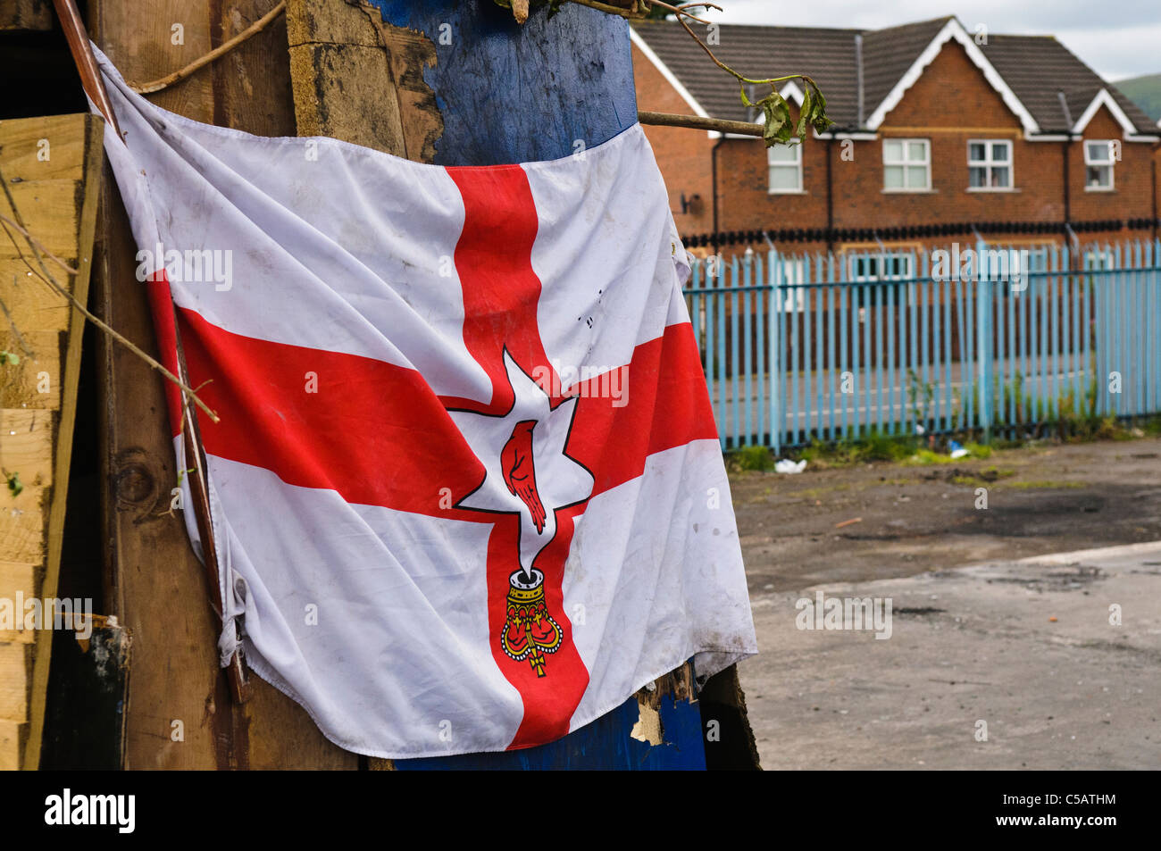 Ulster flag at a bonfire site, hung by protestants upside down, a sign of disrespect. - Stock Image