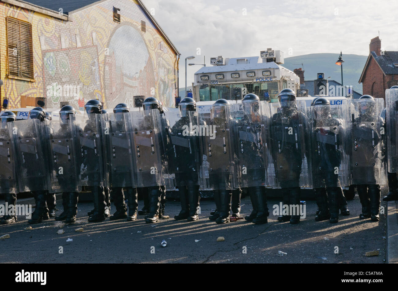 Line of PSNI Officers in riot gear, with armoured landrovers and water cannon. - Stock Image