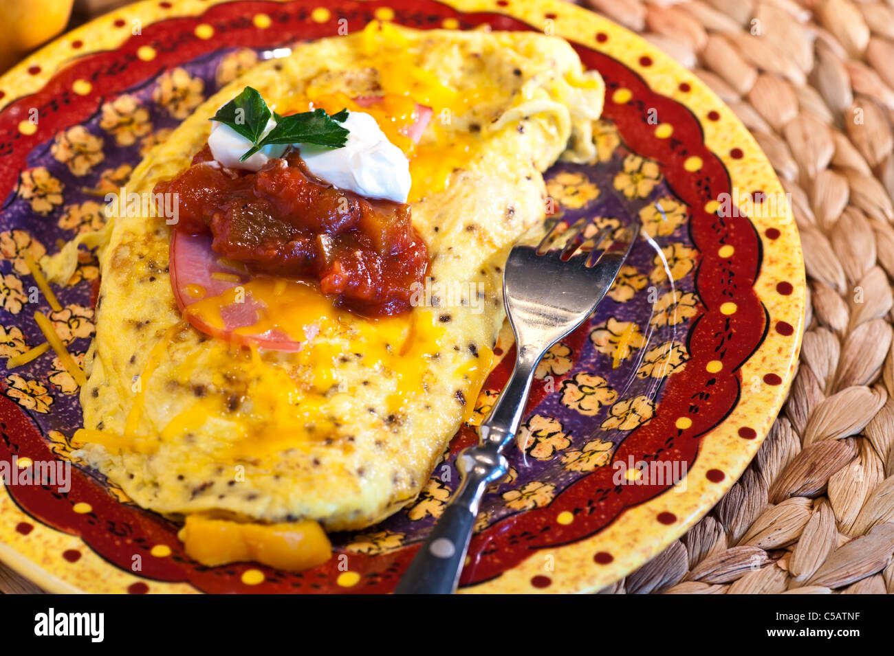 Southwestern Omelet with mushrooms, onions sweet peppers with cheese and Canadian bacon on top. - Stock Image