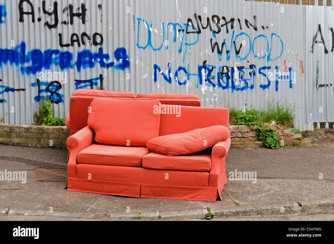Two old red sofas left on a footpath beside a fence with 'No Rubbish' written on it. - Stock Image