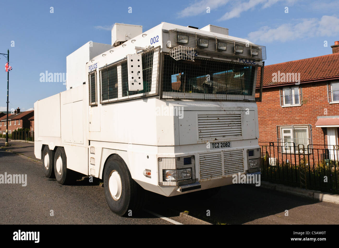 Police water cannon waits at an interface area ahead of expected civil disturbance. - Stock Image