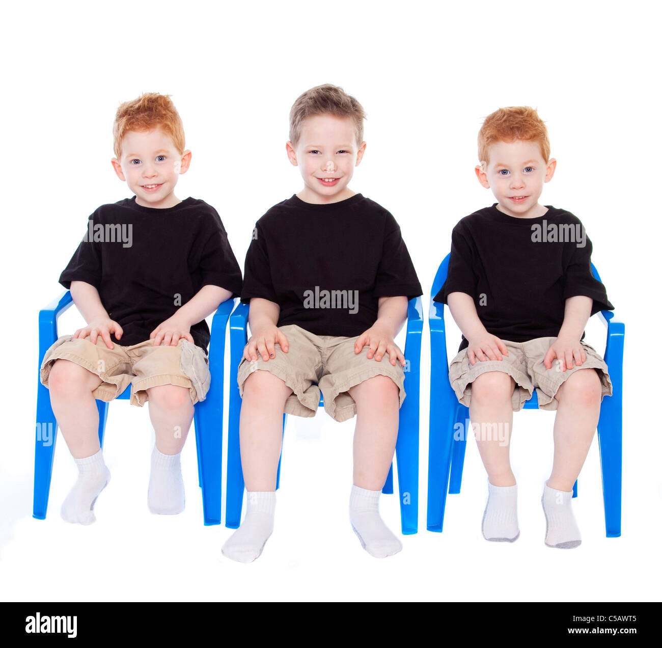 Three boys sitting on blue chairs on white - Stock Image