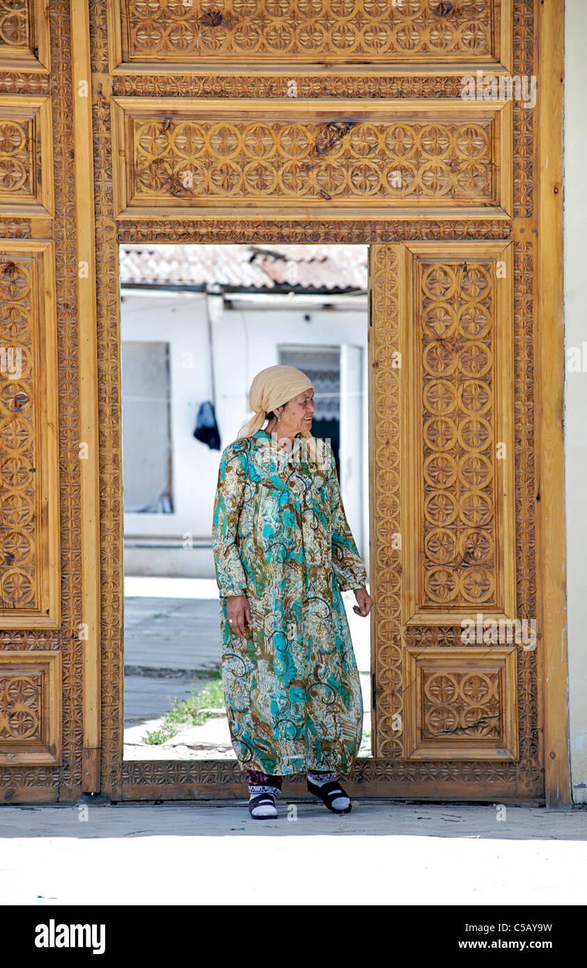 Uzbeki woman outside carved wooden doors, Samarkand, Uzbekistan - Stock Image