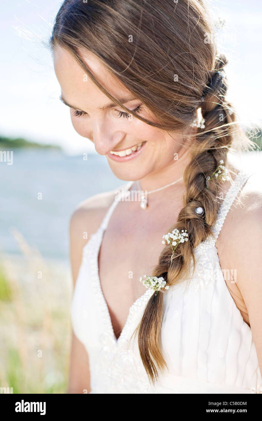 Happy young newly wed woman with flowers in plaited hair on a bright and sunny day - Stock Image