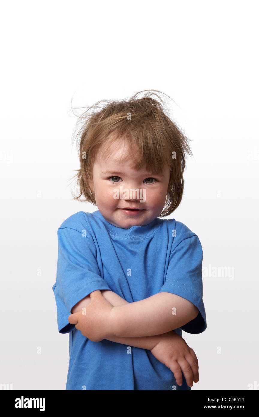 Portrait of a cute little girl in blue t-shirt and with tousled hair standing over white background - Stock Image