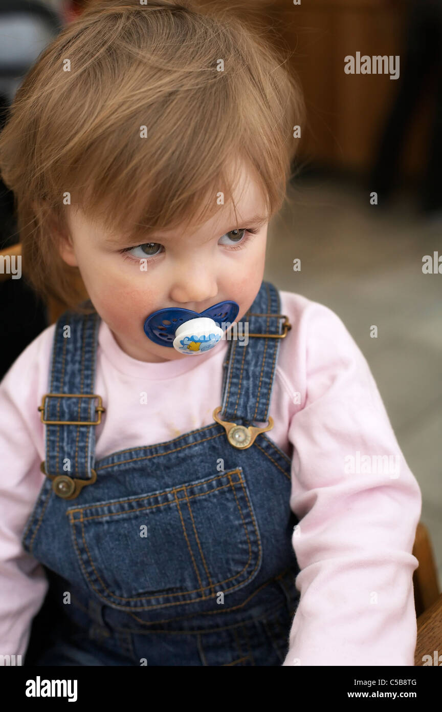 close up of a cute little shy girl with pacifier in her mouth stock