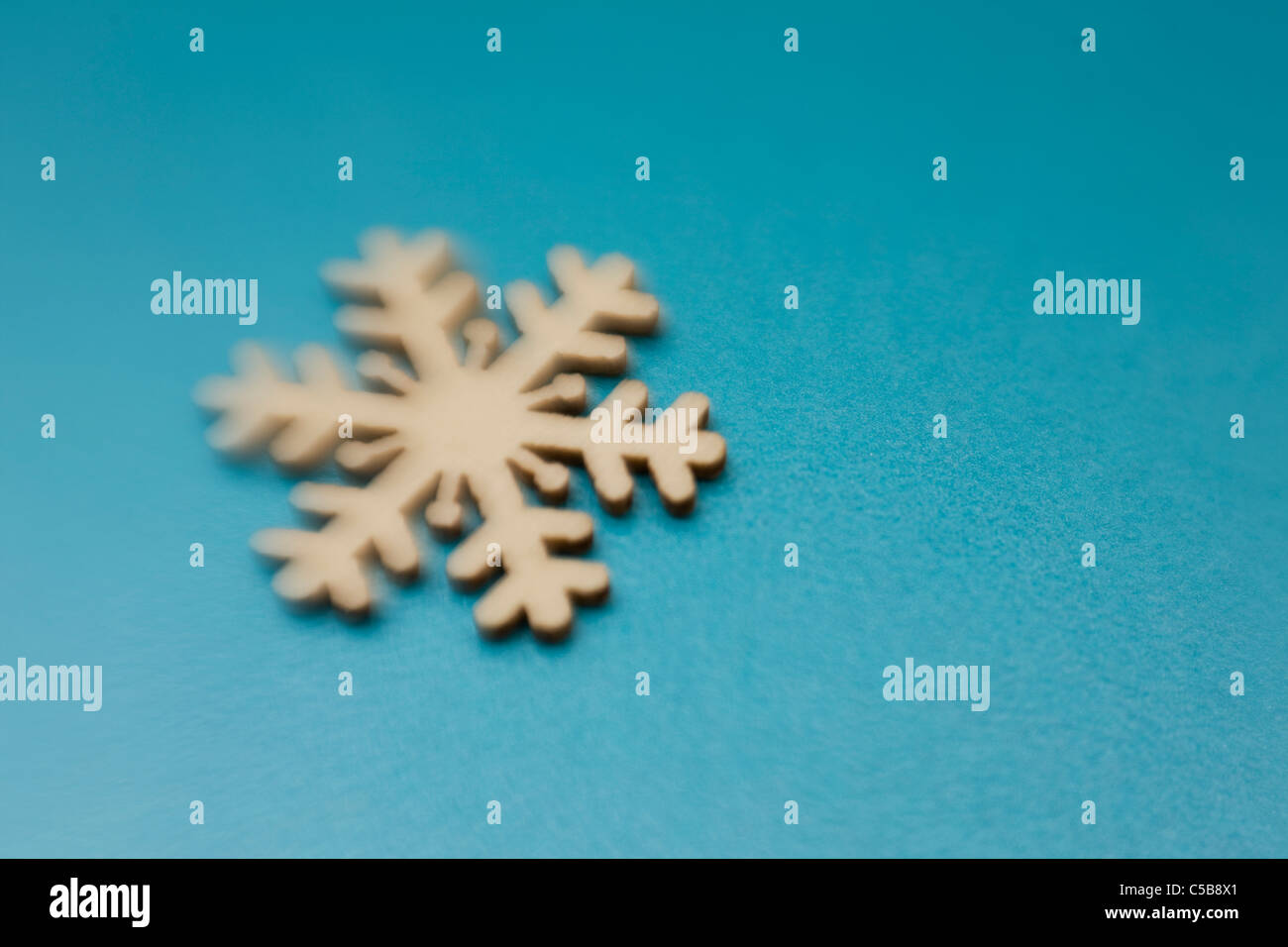 Snowflake ornament on blue background - Stock Image