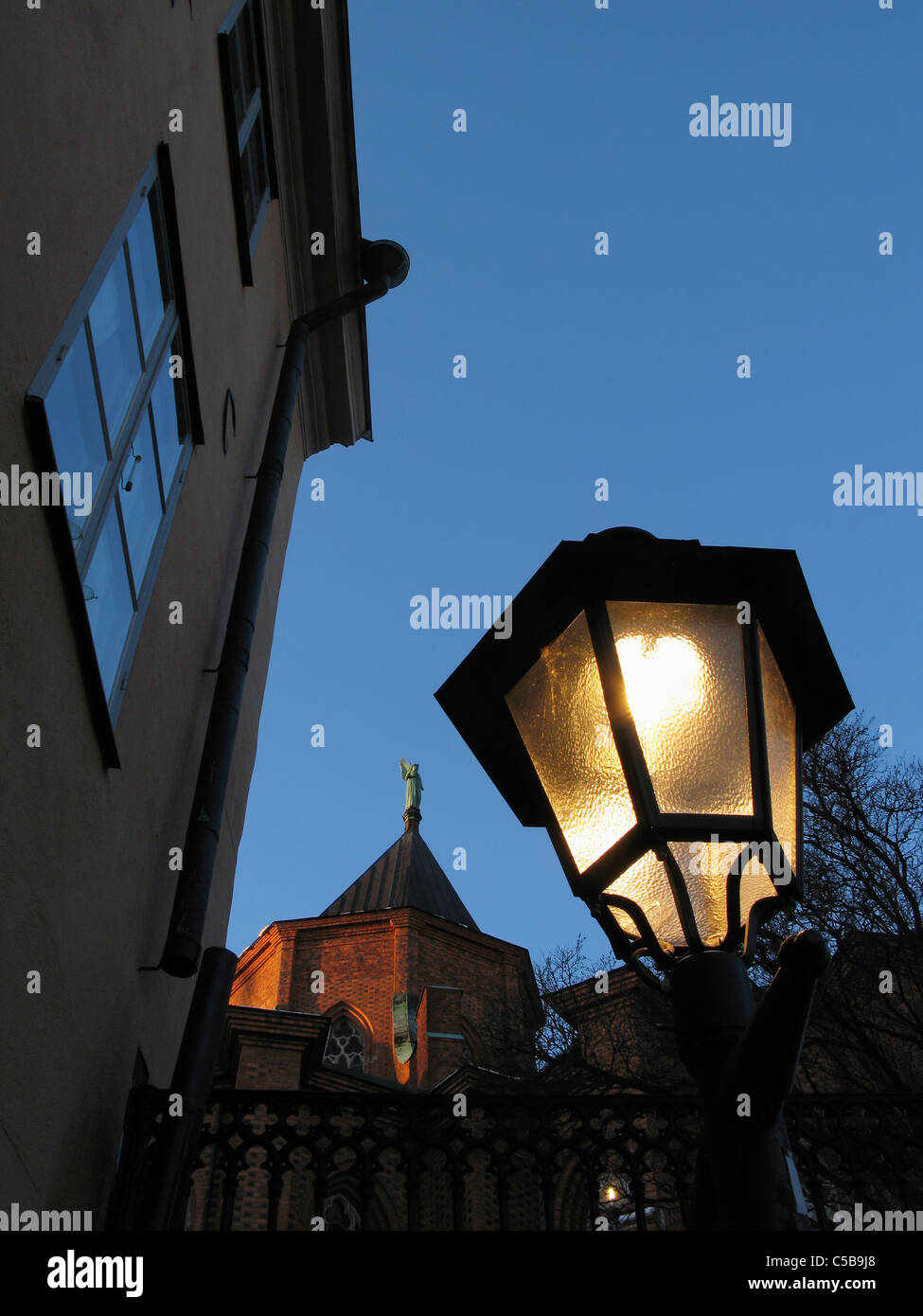 Low angle view of lit streetlight and Uppsala Cathedral against clear blue sky at night - Stock Image