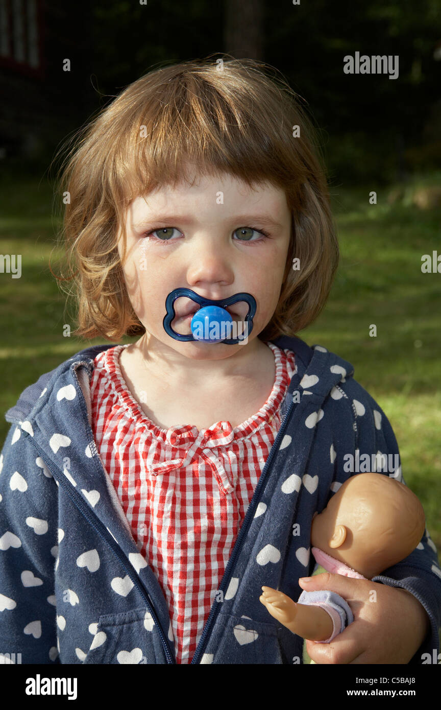 close up of a little girl with pacifier in mouth holding her doll as