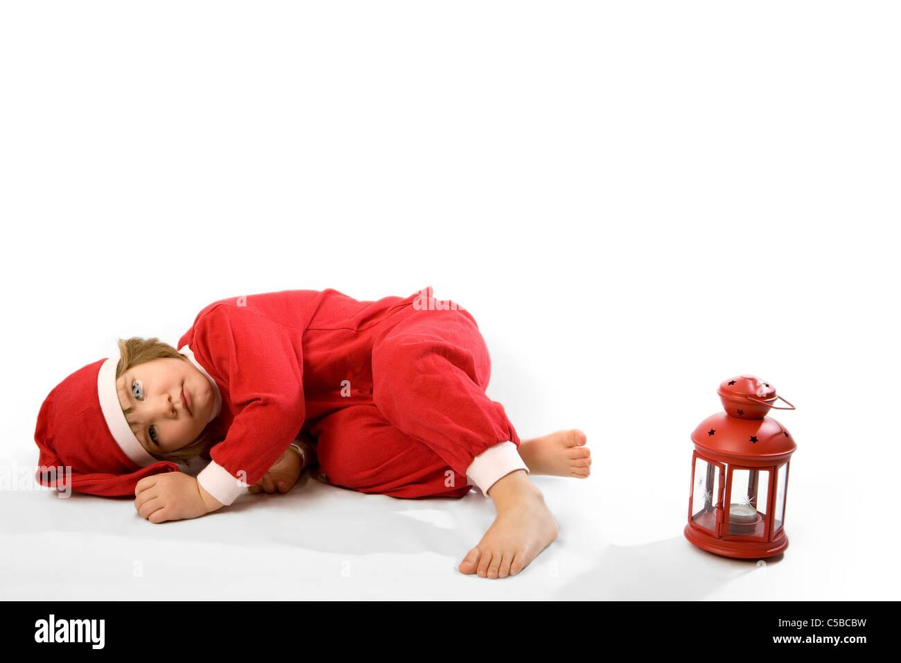Santa girl resting on floor besides a red lantern over white background - Stock Image