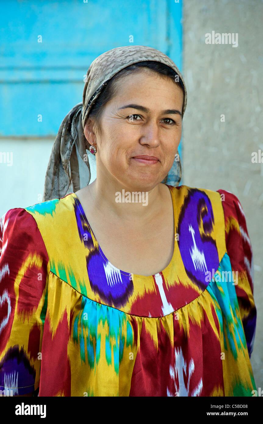 Uzbeki woman in distictive ikat style Uzbeki dress, Urgut market, Samarkand, Uzbekistan - Stock Image