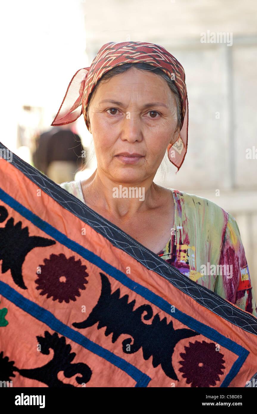 Textile vendor with embroidered suzani textile, Urgut market, Samarkand, Uzbekistan - Stock Image
