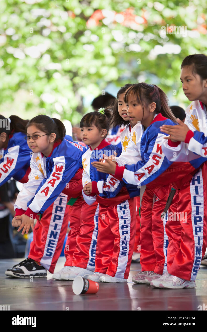 Filipino children bowing during a martial arts display.  The Forks, Winnipeg, Manitoba, Canada. - Stock Image