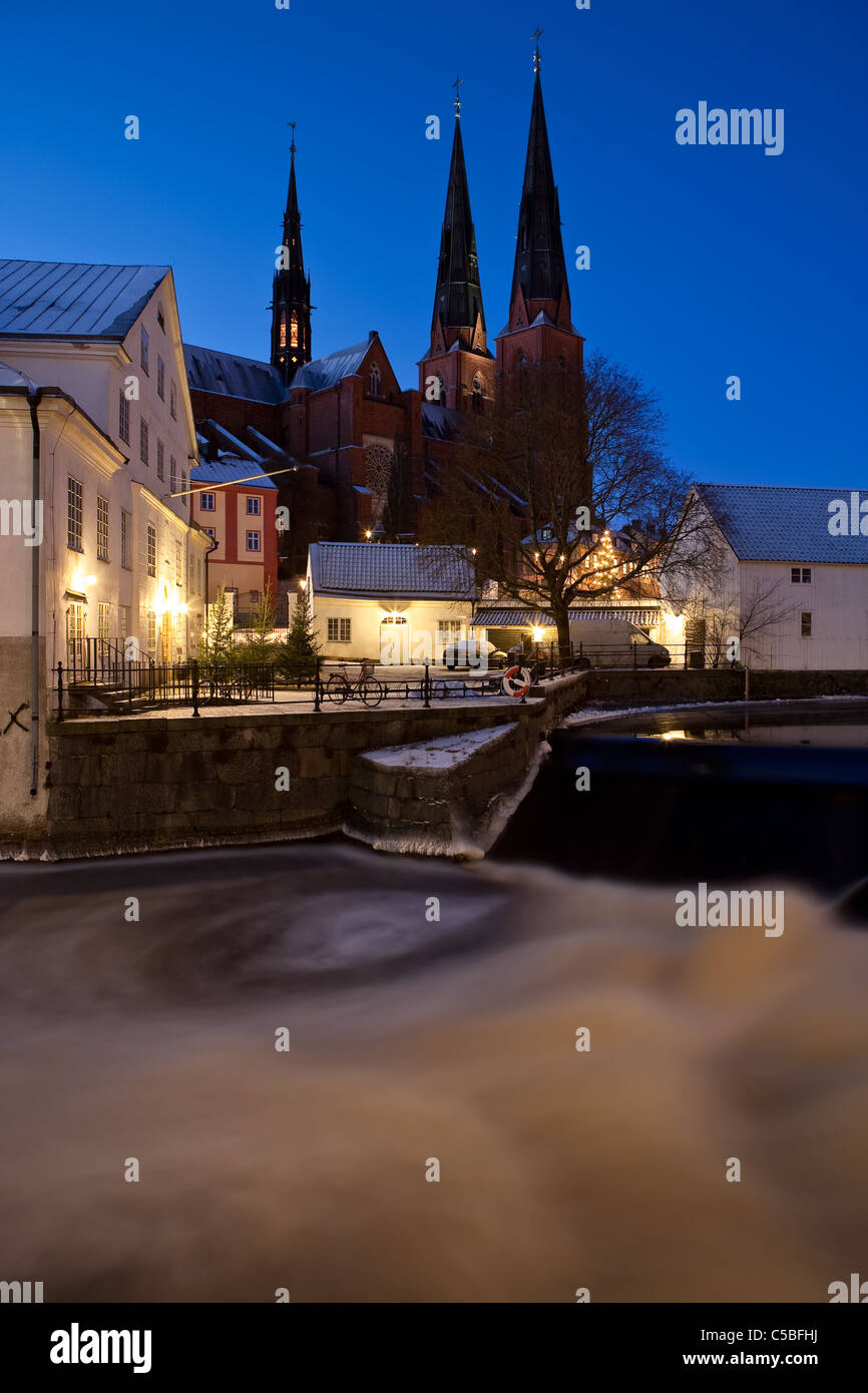 Uppsala cathedral against clear blue sky with Fyrisån in the foreground at night Stock Photo