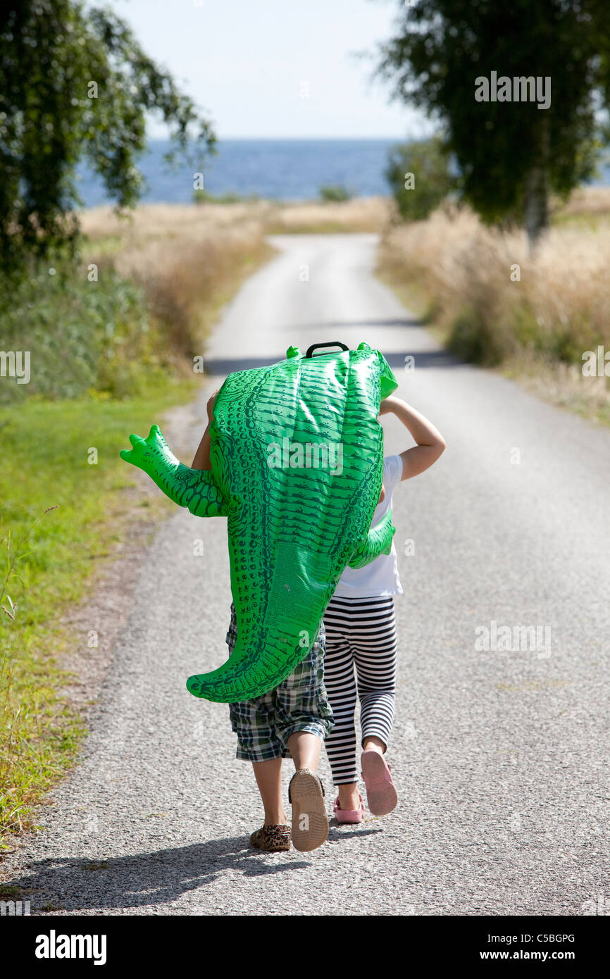 Rear view of two children carrying a toy crocodile on a road leading towards the sea - Stock Image