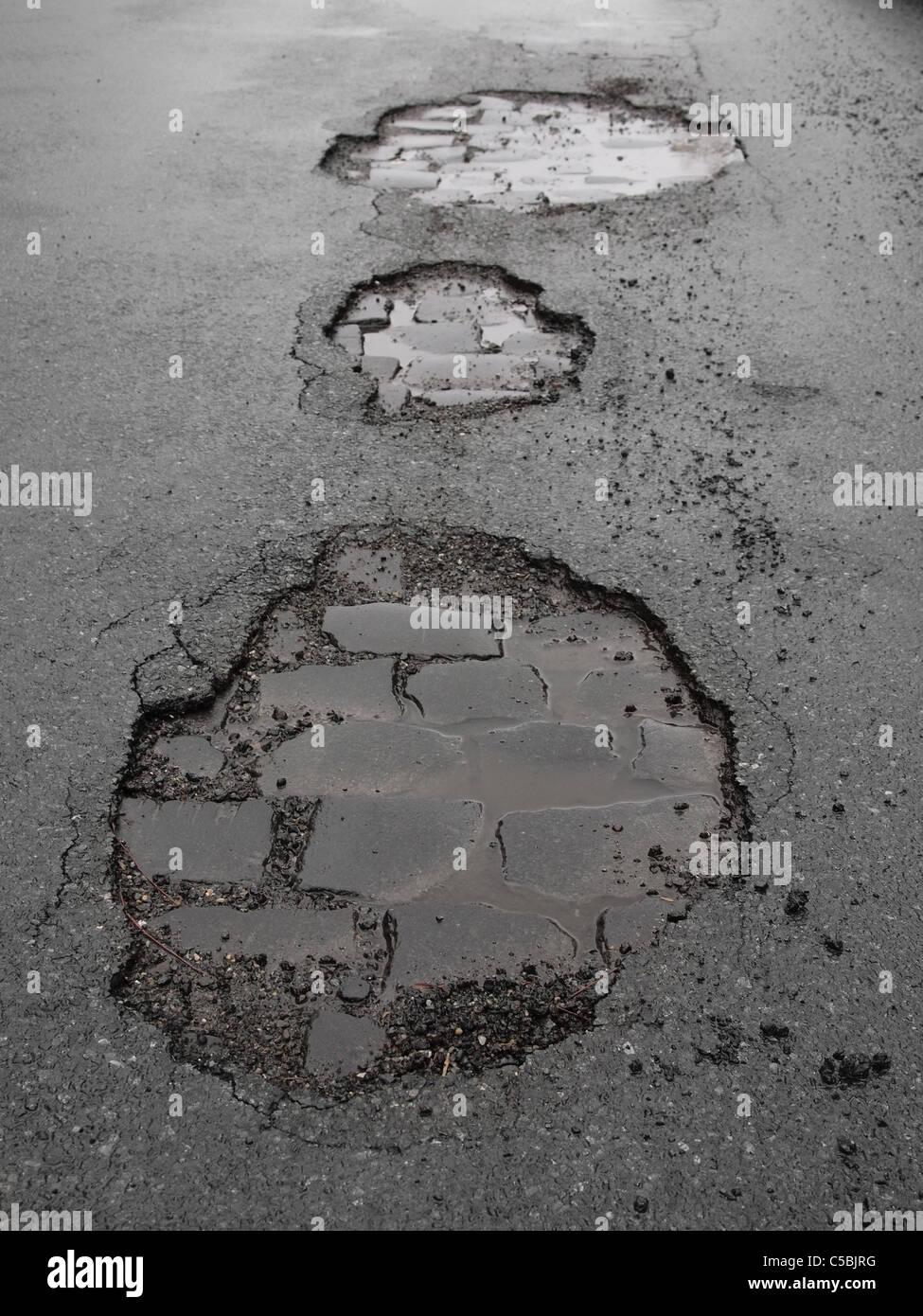 potholes / road damage - Stock Image