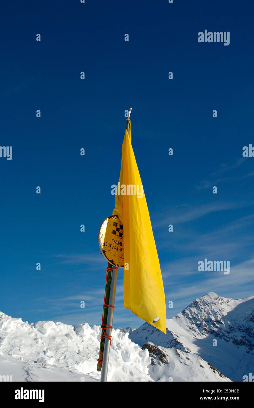 Close-up of yellow flag in snow against clear blue sky - Stock Image