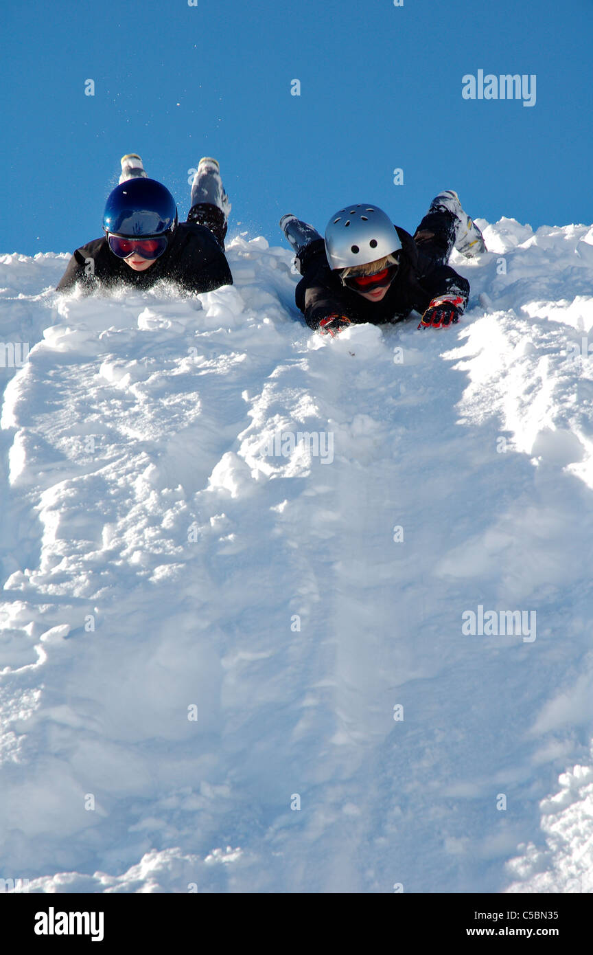 Two children playing in the snow against clear blue sky Stock Photo