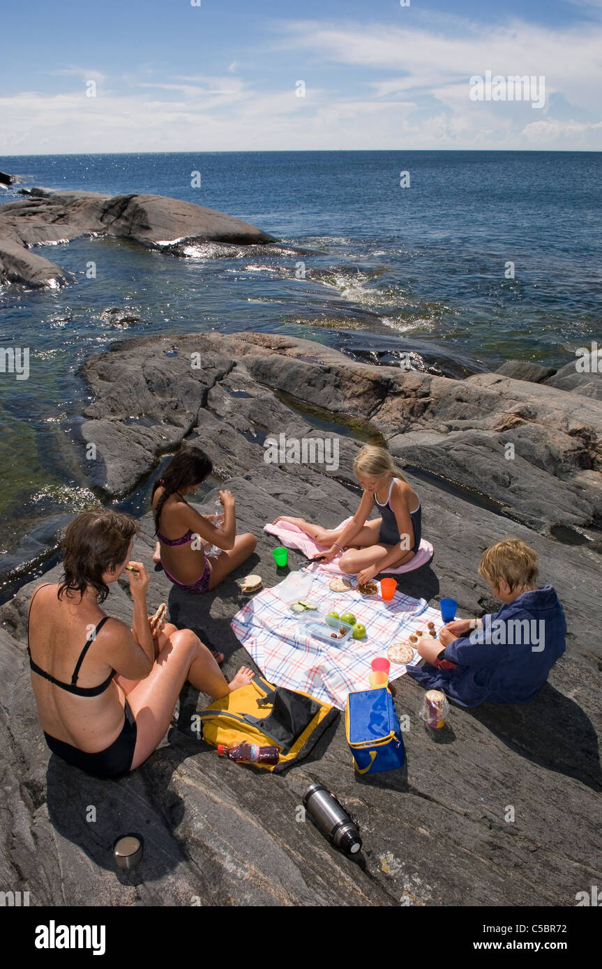 Four friends picnicking on the rocks with sea in the background - Stock Image