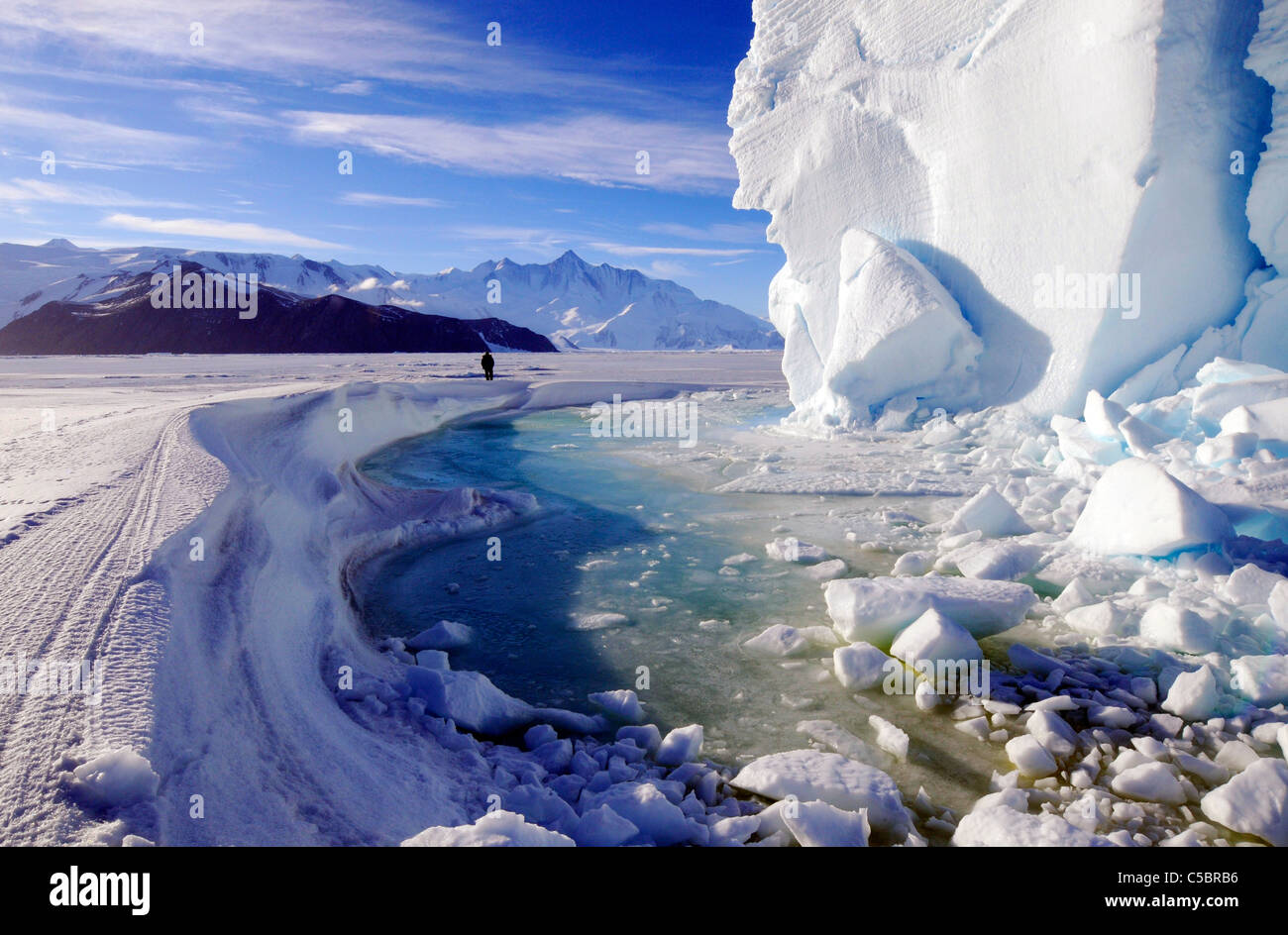 Mount Herschel with person, large ice berg and marine algae in pool near Cape Hallett northern Ross Sea Antarctica - Stock Image