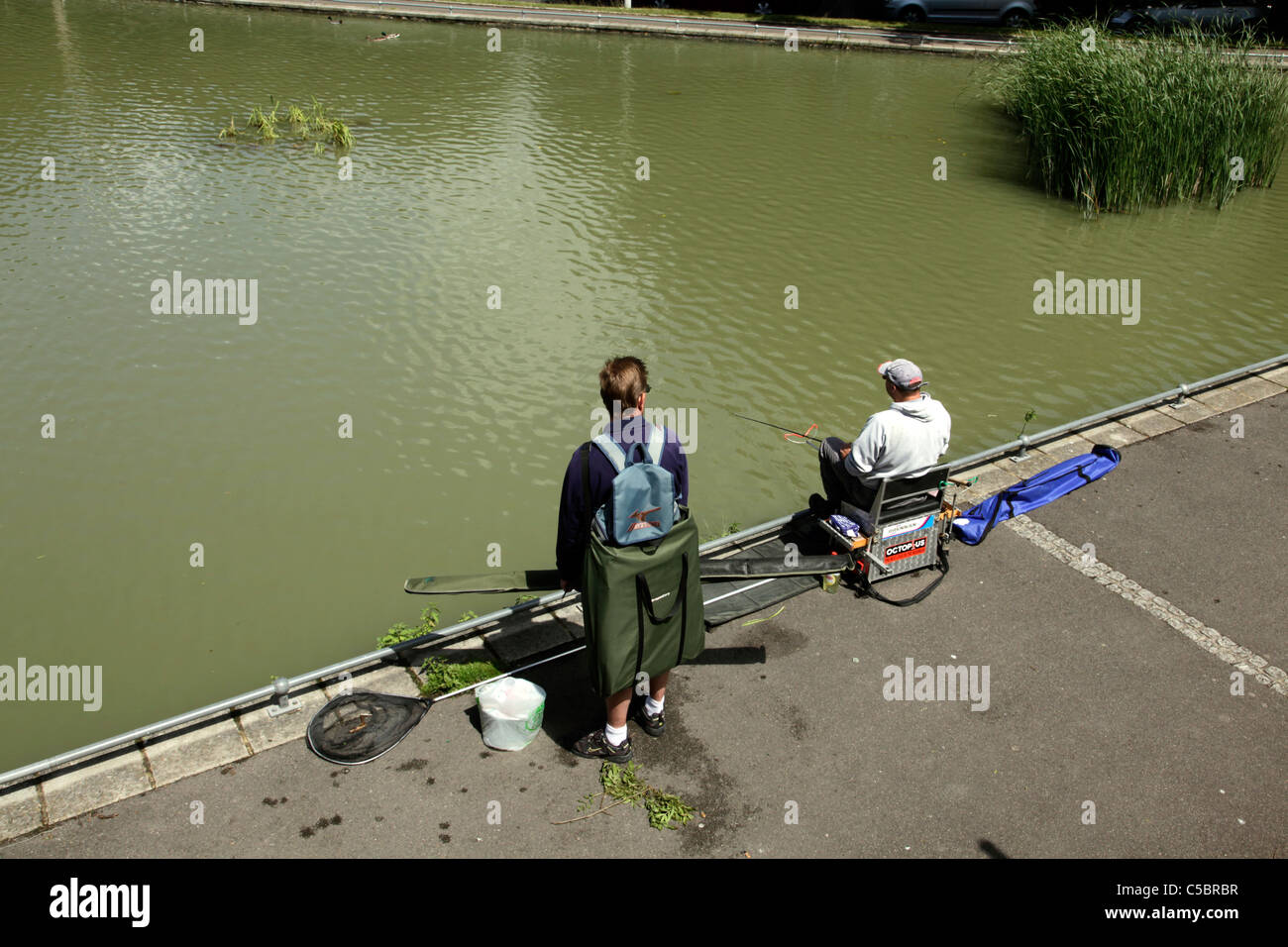 Two anglers at fishing pond adjacent to Radnor Park Folkestone - Stock Image