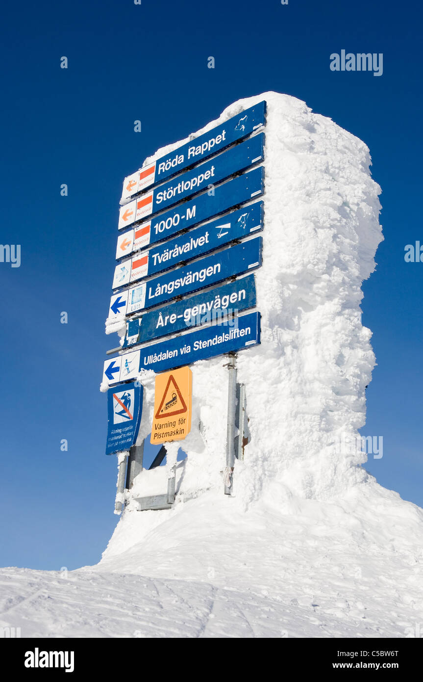 Frozen signboards in winter against clear blue sky - Stock Image