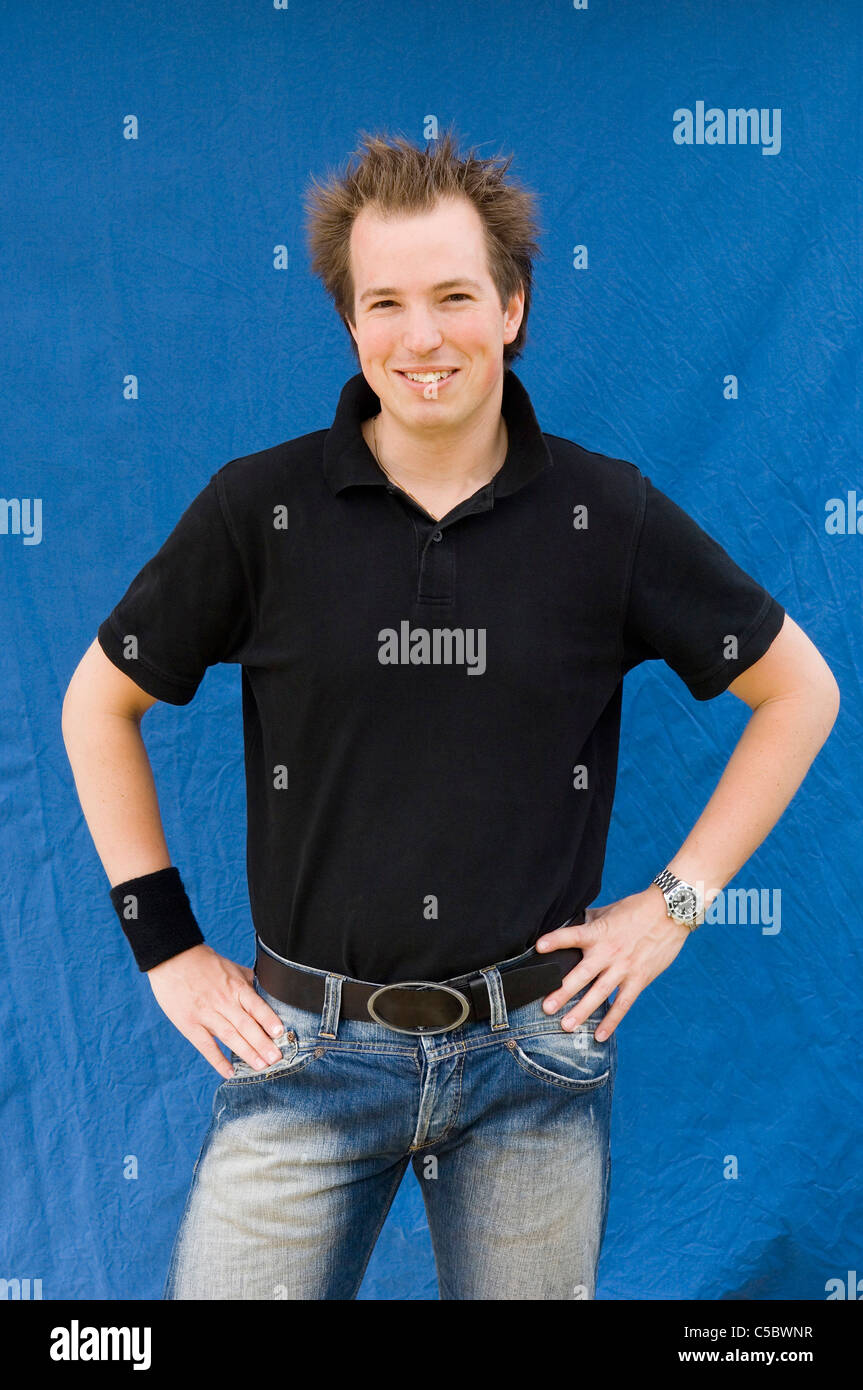 Portrait of a young man in casuals standing with hands on hips over blue background - Stock Image