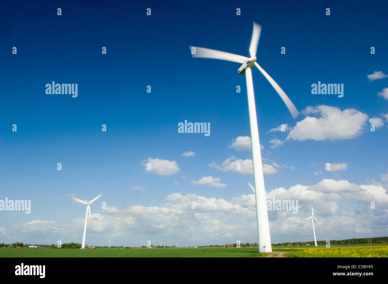 Low angle view of wind turbines on peaceful landscape against the sky - Stock Image