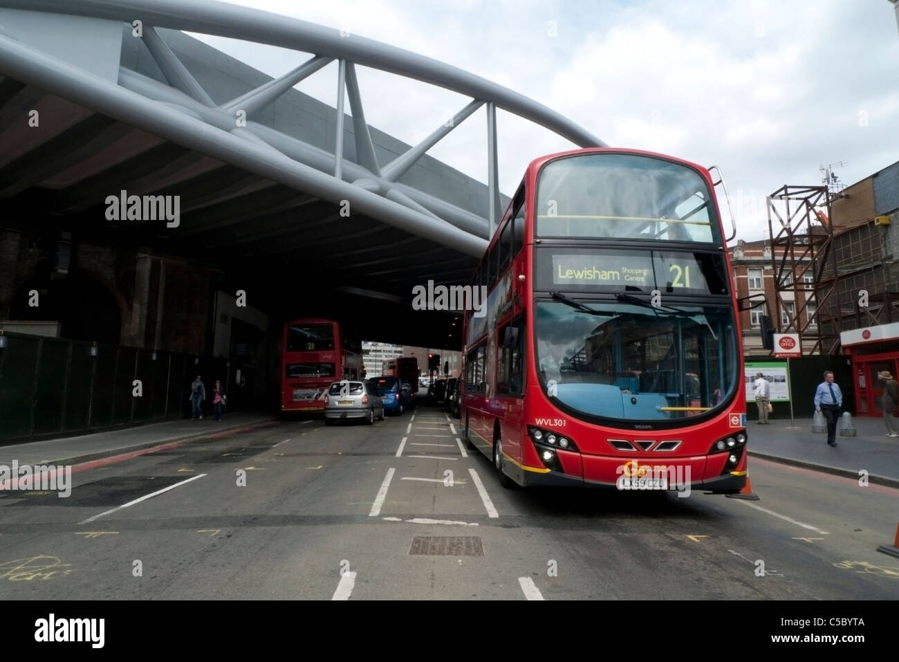 A red double-decker 21 bus destined for Lewisham passing under Network Rail new railway Viaduct Bridge at London Stock Photo