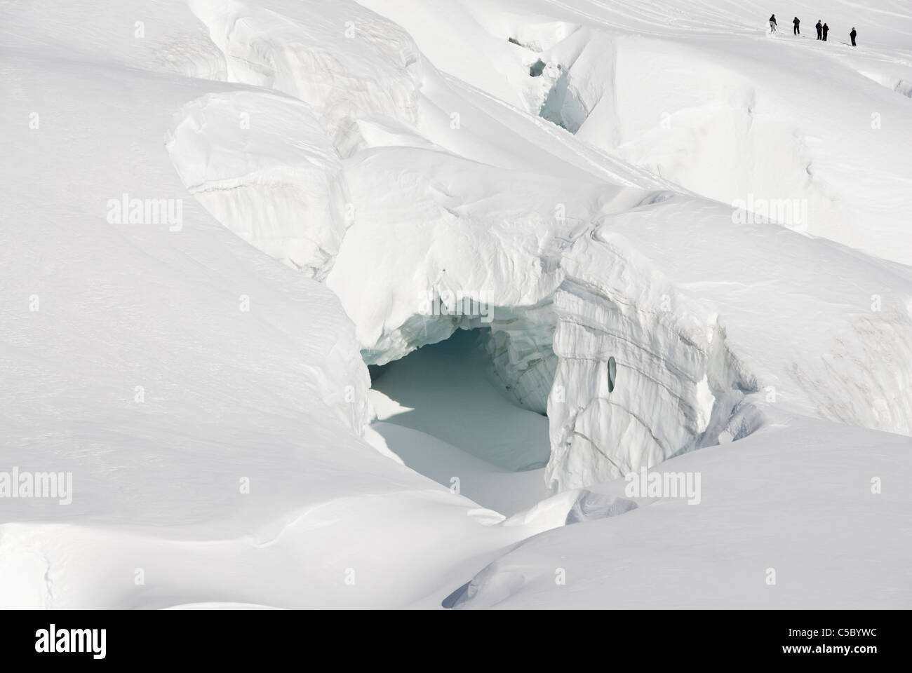 Distance shot of skiers with glaciers in foreground - Stock Image