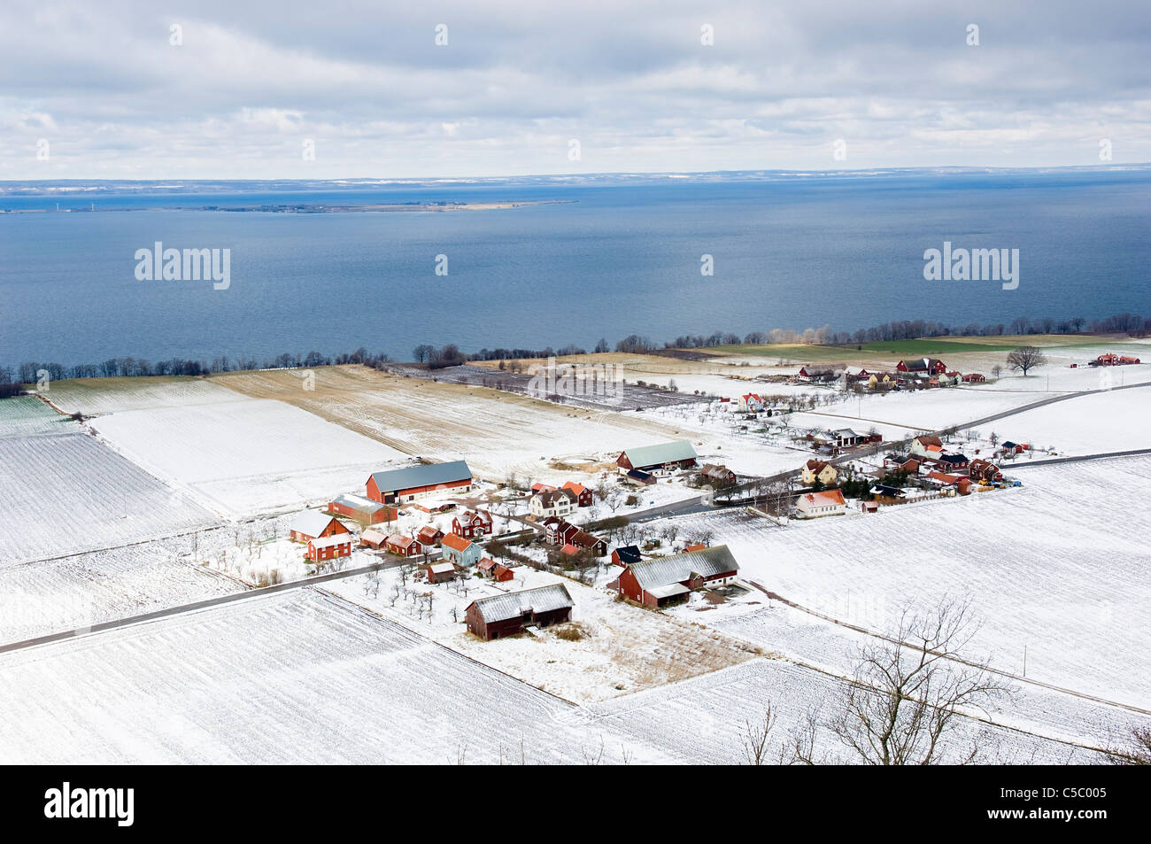Wintery landscape by Vattern lake below cloudy sky - Stock Image