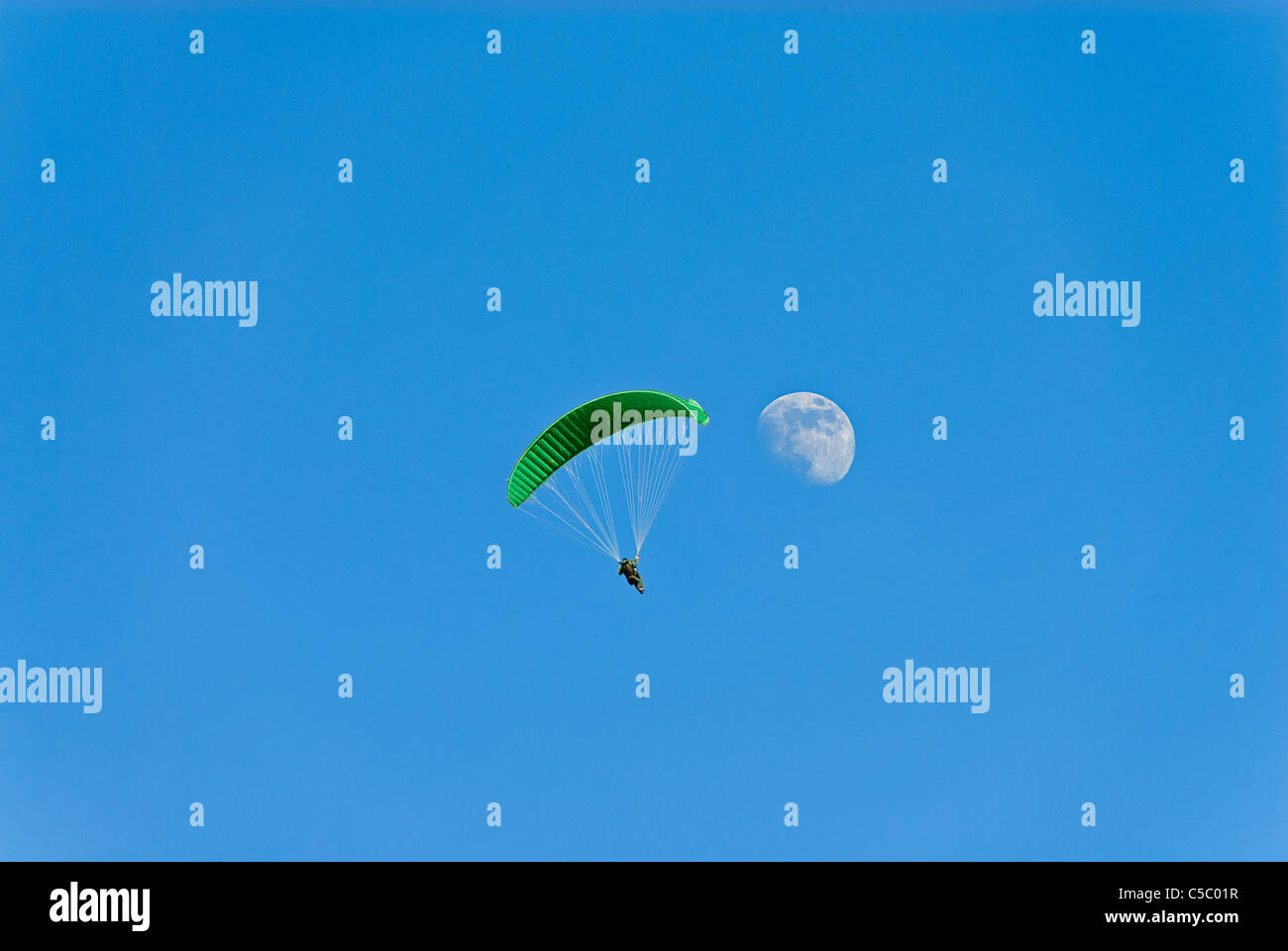 Low angle view of hang gliding by the moon against clear blue sky - Stock Image