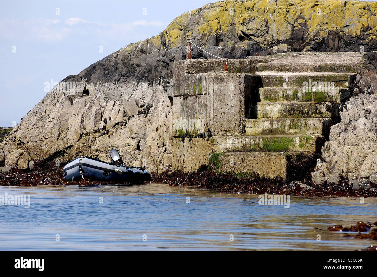 Landing stage on the Farne Islands with dinghy and outboard motor tied up at foot of it. - Stock Image