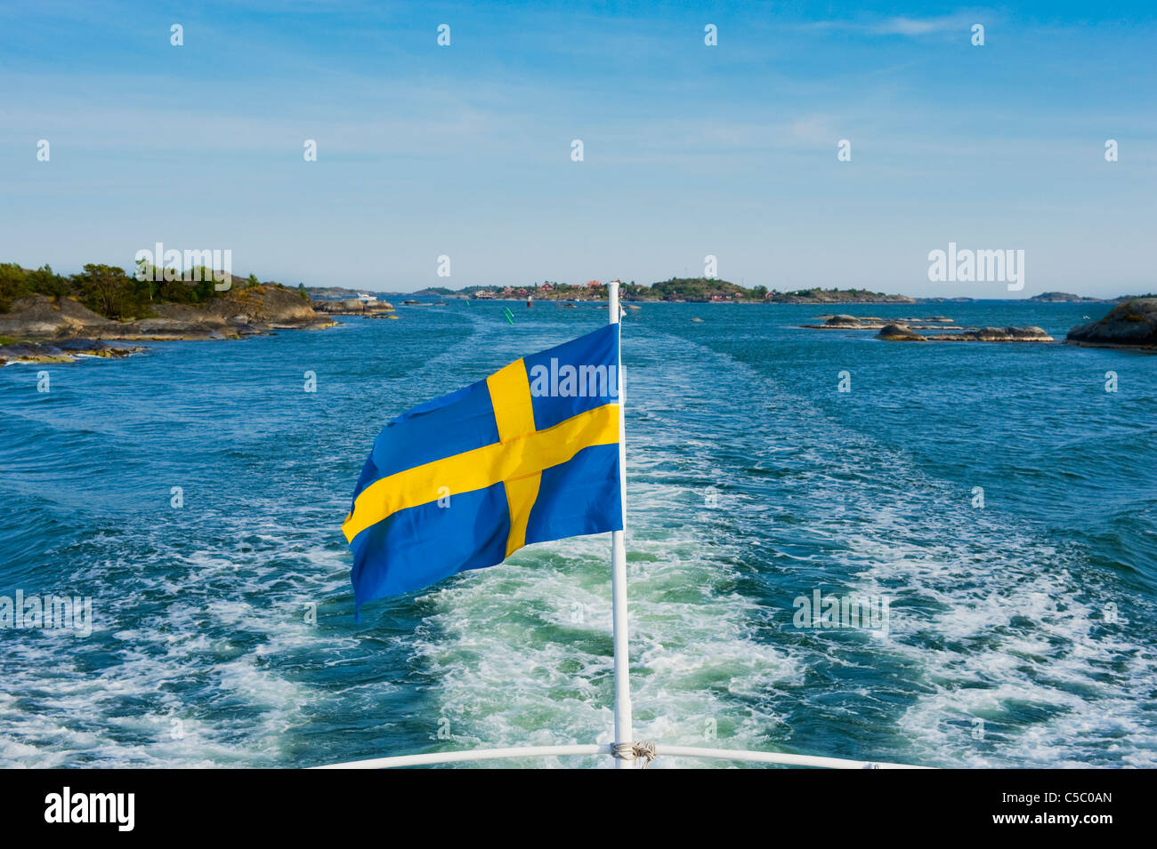 Swedish flag fluttering against the sea and blue sky - Stock Image