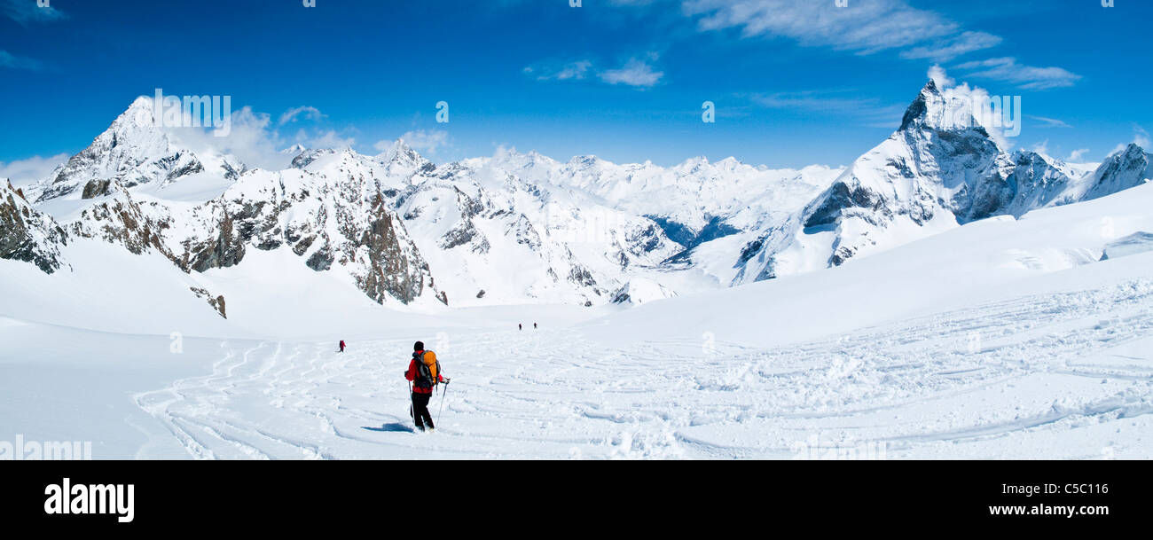 Mid distance of off piste skiing against blue sky at Matterhorn - Stock Image