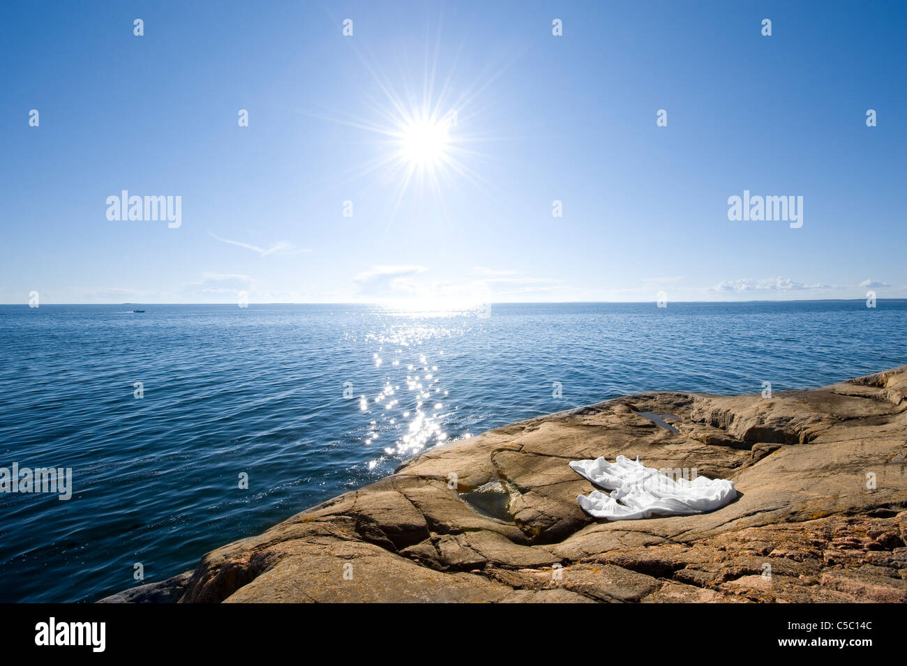 Cliff by the scenic and peaceful sea on a sunny day - Stock Image